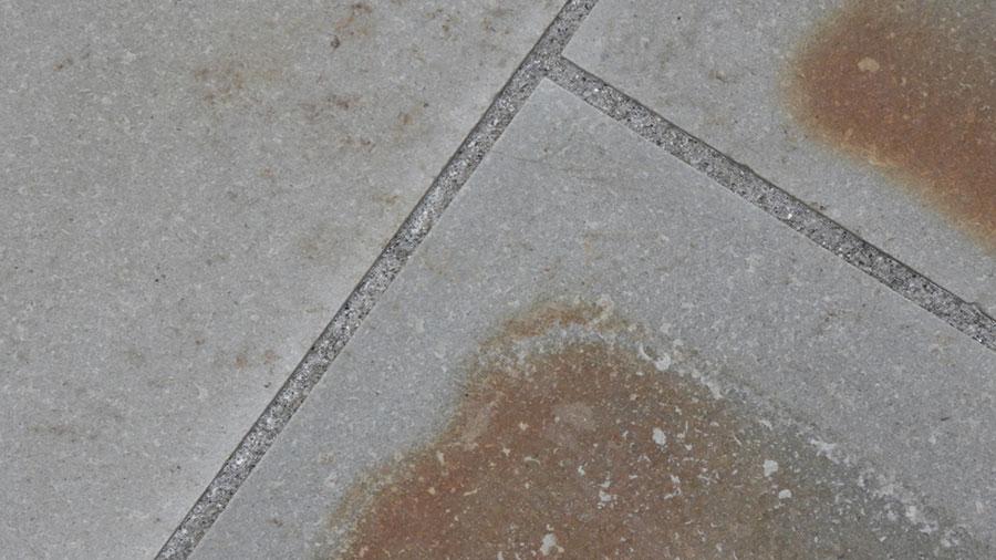 Sachverständiger beurteil den Mangel an einem Bodenbelag. Flecken auf Bodenfliesen im Außenbereich